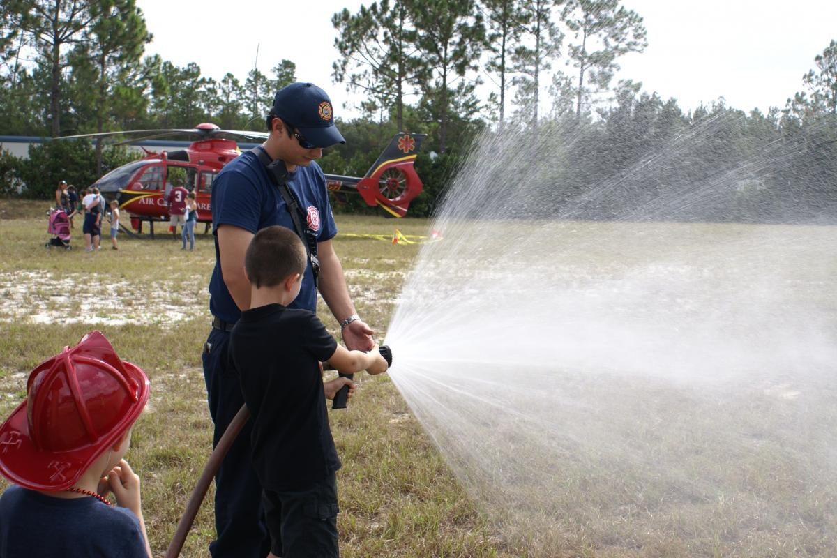 Child spraying fire hose with a firefighter